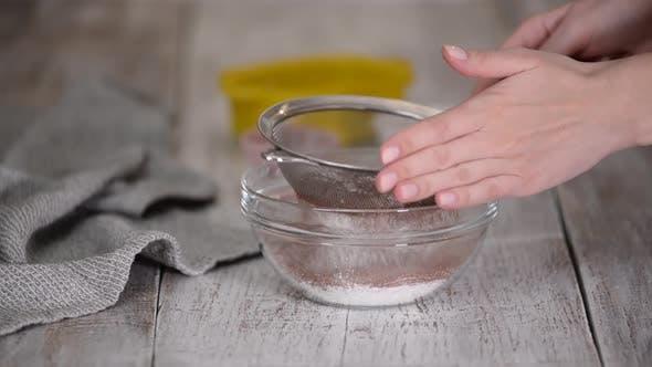 Woman Hands Sieben von Mehl und Kakaopulver