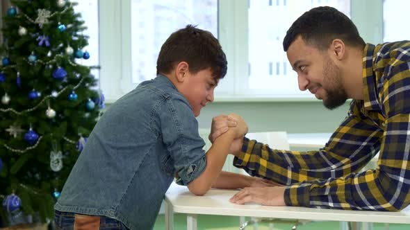 Thumbnail for Father and Son Armwrestle on the Table
