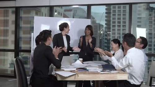 Successful Asian Business People Celebrate Project Success in Group Meeting