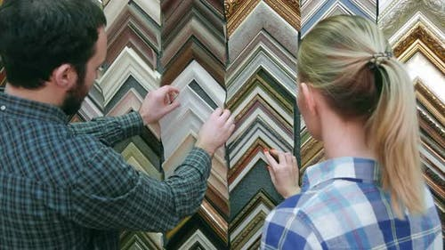Young Couple Customer Looking for Frame for Picture in Atelier