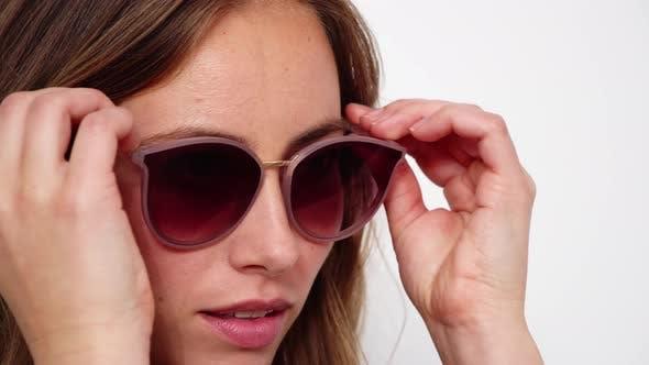 Thumbnail for Brunette Putting on Sunglasses