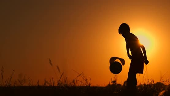 Cover Image for Silhouette of a Boy Playing Football or Soccer at the Beach with Beautiful Sunset Background