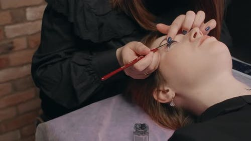 Lashmaker Does the Eyelash Lamination Procedure for the Client in the Beauty Salon Cosmetic Services