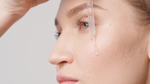 Beautiful Young Woman Applying Skincare Serum on Her Face Close Up