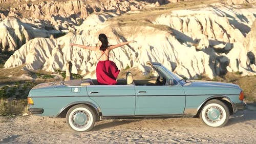 Sexy Woman in Red Dress is Watching the Sandstone Hoodoos Landscape in Old Classic Blue Car