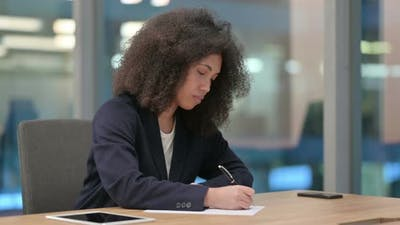 Hardworking African Businesswoman and Writing on Paper