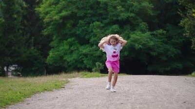 Girl playing and running in the park. Funny little child running along the path