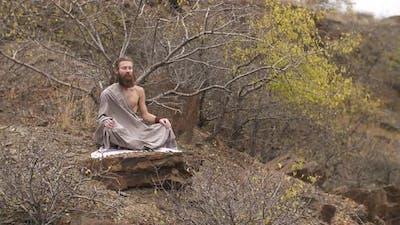 Buddhist Meditates on the Rock