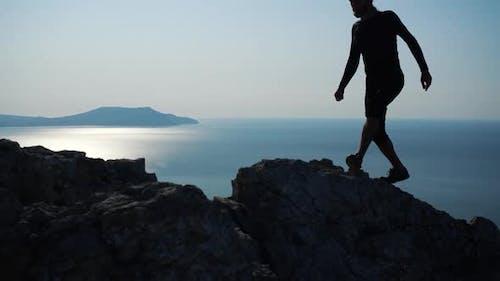 Junge langhaarige inspirierte Mann hebt seine Hände hoch stehend auf dem Gipfel eines Berges über dem Meer