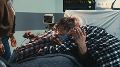 Elderly Man Hugging Family in Hospital Ward