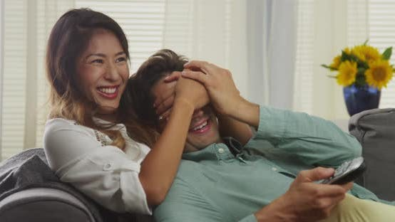 Thumbnail for Japanese woman covering boyfriend's eyes from the tv