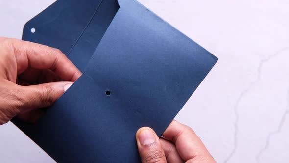 Person Hand Putting Cash in a Envelope.