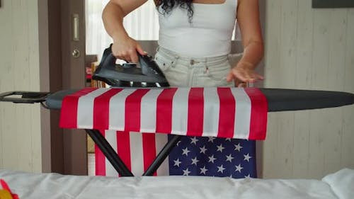 Patriotism Independence Day and Holidays Concept Young Woman Ironing the National American Flag at