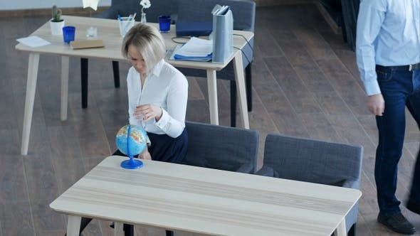 Thumbnail for Calm single young woman relaxing at work looking at globe