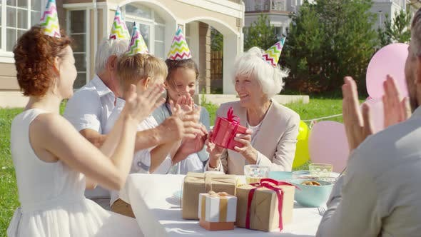 Thumbnail for Grandmother Receiving Birthday Present from Family on Outdoor Party