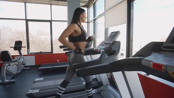 Thumbnail for Attractive Girl Running on Treadmill in the Gym Body Training Cardio