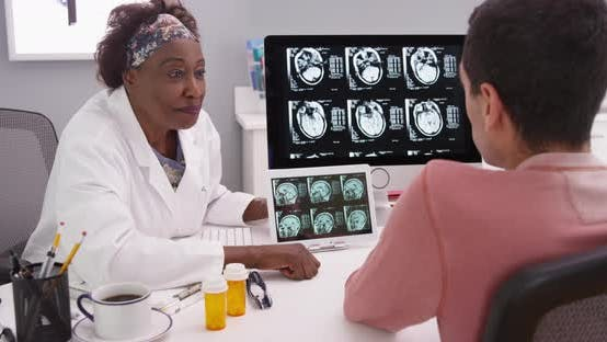 Senior African physician explaining to male patient effects of a concussion