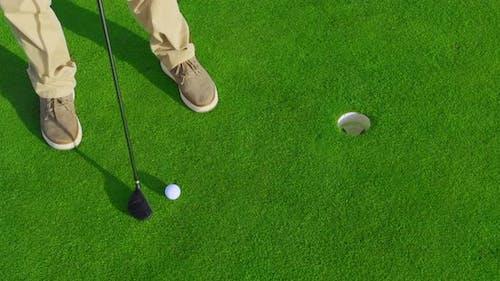 Adult Man Hitting a Golf Ball on Tee with Sunset. Closeup