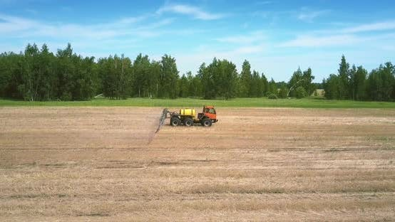 Tractor Trailer for Spraying Fertilizers Moves on Harvested Field