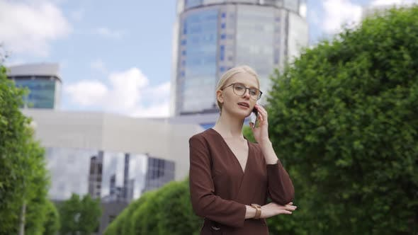 Young Business Woman Makes an Appointment By Phone Against the Backdrop of Skyscrapers
