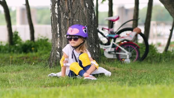 Thumbnail for Cute blonde girl sitting under the tree wearing bicycle helmet