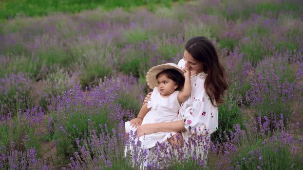 Woman Hugging and Kissing Baby Daughter in Lavender Field