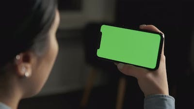 Close up Horizontal hands holding smartphone with green screen. Green screen mobile phone