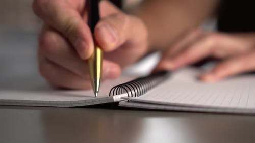 A man writes with a yellow black pen in an open notebook on a gray table