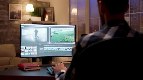 Thumbnail for Back View Dolly Shot of Videographer Using Post Production Software