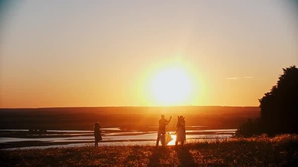 Thumbnail for Young Happy Family Playing with a Kite on the Field While the Bright Orange Sunset