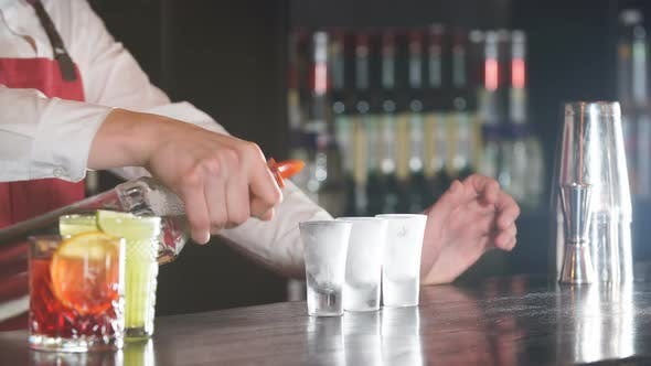 Thumbnail for Bartender Pouring Some Drink From Bottle Into Shot Frozen Glasses