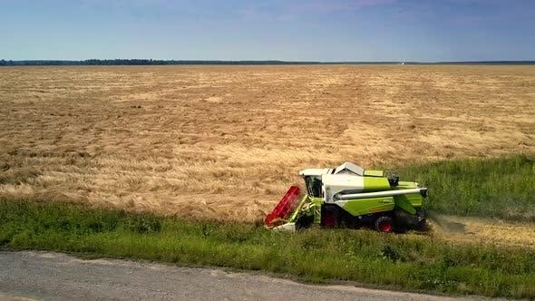 Thumbnail for Harvester Moves Along Farmland Cutting Off Ripe Grain