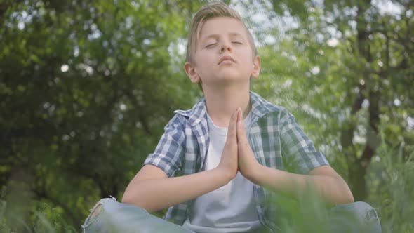 Cover Image for Cute Little Handsome Boy Sitting on the Grass Meditating. Child Practices Yoga. The Spiritual