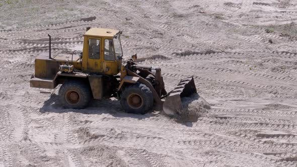 Thumbnail for Old Tractor on Rubber Wheels Moves Sand Using a Bucket on Construction Site