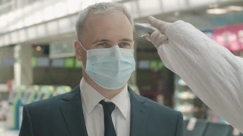 Close-up Portrait of Mid-adult Businessman in Face Mask Standing in Airport Departure Area As