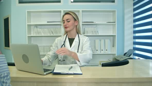 Thumbnail for Smiling Nurse with Laptop Scheduling Appointment for Male Patient at Reception