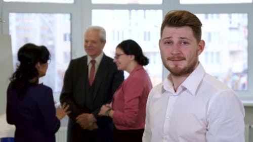 Young Guy Looks at Business People