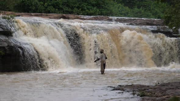 Man fishing around the Farako falls
