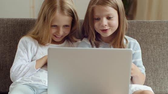 Thumbnail for Vue de face de deux petites écolières amies assis ensemble sur le canapé à la maison devant l'ordinateur portable