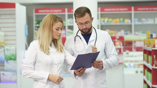 Two Pharmacists Are Discussing Medication Working in Pharmacy.
