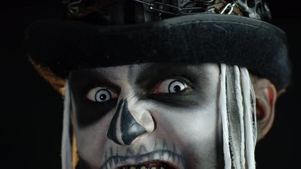 Sinister Man with Horrible Halloween Skeleton Makeup Making Faces, Showing Teeth, Trying To Scare
