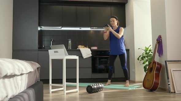 Thumbnail for Multitasking sporty fitness. Woman doing squats with smartphone in hands at home in kitchen