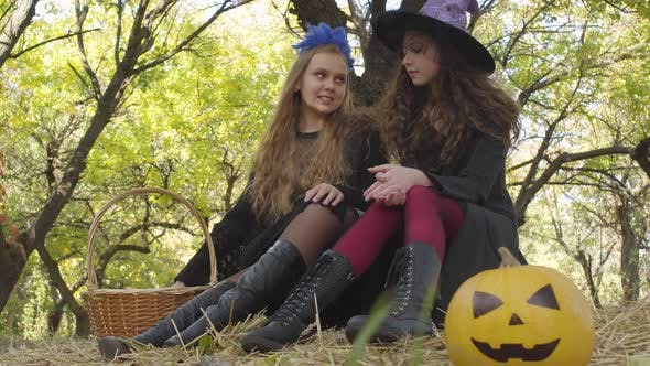 Thumbnail for Two Pretty Caucasian Girls in Halloween Costumes Sitting in the Autumn Forest and Chatting