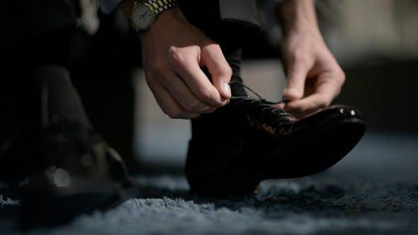 Thumbnail for Mann binden Schuhe