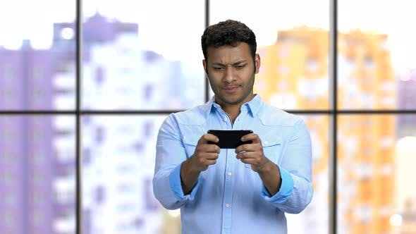 Expressive Young Darkskinned Man Plays Smartphone Game