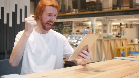 Cover Image for Excited Redhead Beard Man Celebrating Success, Sitting in Cafe