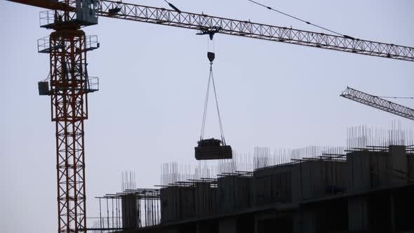 Thumbnail for Tower Crane on a Construction Site Lifts a Load at High-rise Building.