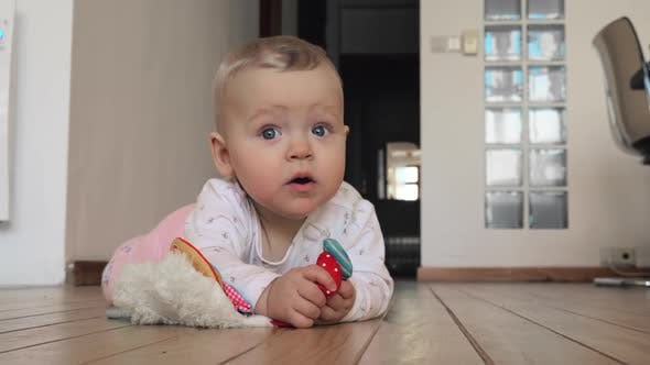 Thumbnail for Sweet Blue-eyed Baby Girl with Toy on the Floor at Home