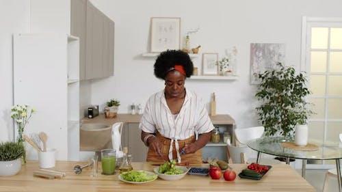African American Woman Making Salad at Kitchen