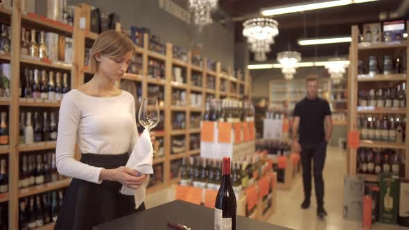 Thumbnail for Girl in White Shirt and Black Skirt Rubbing Wine Glass in a Wine Shop